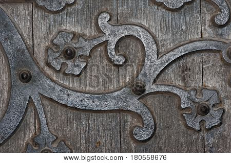 a fragment of ancient ornate ironwork on wooden door in Lisbon, Portugal