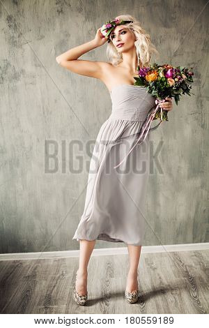 Summer Beauty Portrait of Beautiful Blonde Model Woman with Blonde Hair Blowing Dress and Flowers