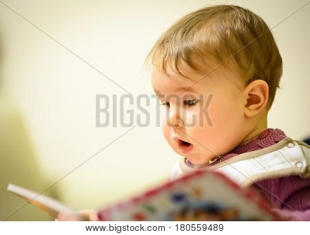 Baby girl reading a children's book in the room