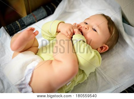 Baby hugged his leg and sucking toe