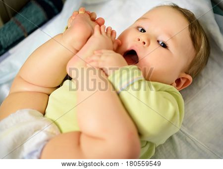 The child grabbed his legs and wants to suck toes