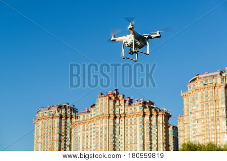 Drone quad copter with onboard high resolution digital camera flying over the city in the blue sky