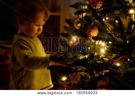 Baby looks at decoration on a Christmas tree at home. The one-year child during the Christmas and New Year holidays.