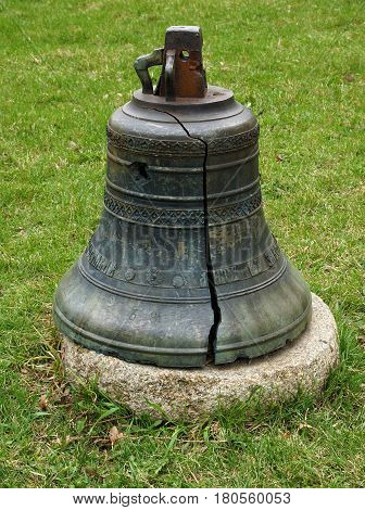 An antique bronze bell with a crack on the territory of the church in Kiev Ukraine