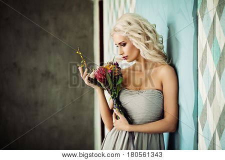 Beautiful Blonde Model Woman with Blonde Curly Hairstyle and Flowers on Background