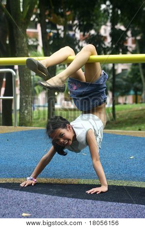 A young girl hangs upside down on a playground bar, balancing as not to fall off