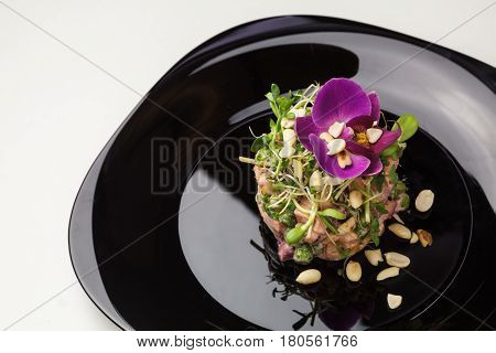 Tasty Tartar (raw Beef) With Sprouts, Peanuts, Greens And Orchid Flower On A Black Plate