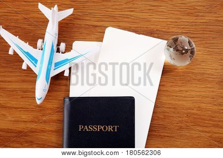 boarding pass and passport with toy plane and glass globe