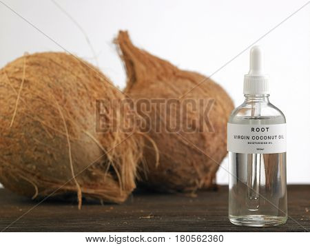 whole coconut and bottle of virgin coconot oil on the white background
