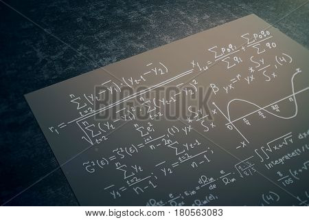 Close up of black paper sheet with mathematical formulas placed on dark desktop. Math concept. 3D Rendering