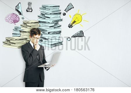 Businessman using laptop on concrete background with drawn paperwork pile. Workload concept