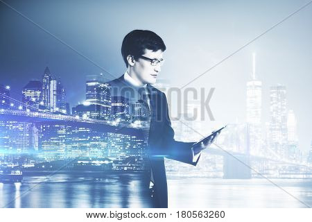 Side view of young european businessman using digital tablet on night city background. Communication concept. Double exposure