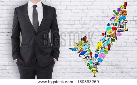 Young businessman on white birck background with business sketch. Approval concept