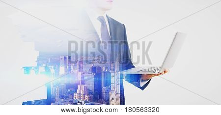 Side view of young businessman with laptop on abstract city background. Communication concept. Double exposure