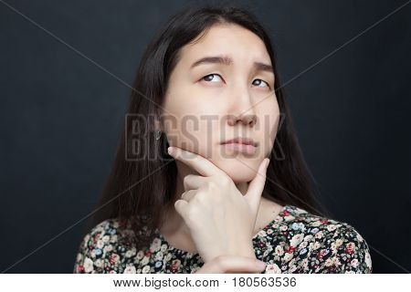 Beautiful Asian Girl Looks Up Thoughtfully, Doubting The Decision. She Rubs Her Chin In Uncertainty