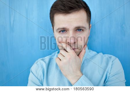 Portrait Of Handsome Man In Blue Shirt. He Looks Seriously In Camera And Rub His Chin