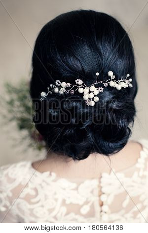 Bridal or Prom Hairstyle with White Pearls Hairdeco on Black Hair of Brunette Woman