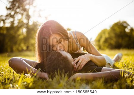 Young multi racial couple kissing in nature on grass - woman lies on man