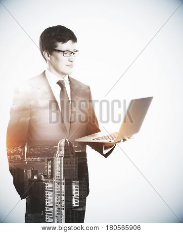 Side view of handsome businessman with laptop on abstract city background. Technology concept. Double exposure
