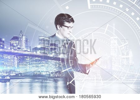 Side view of young european businessman using digital pad on night city background. Communication concept. Double exposure