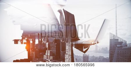 Side view of young businessman with laptop on abstract city background. Work concept. Double exposure