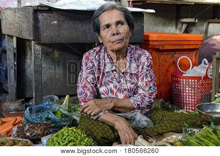 Phnom Penh, Cambodia - December 31, 2016: Unidentified elder woman selling vegetable in Toul Tom Poung Market, also called Russian Market
