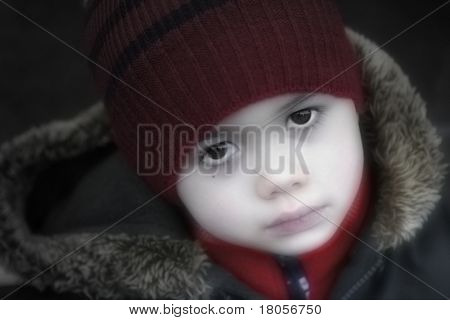 A boy looking melancholy in his winter clothes outside in the park