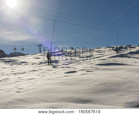 Skier on a ski lift piste in snowy winter alpine mountain resort