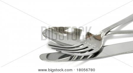 A set of stainless steel knife, fork and a spoon on white background with copyspace.