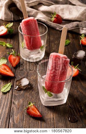 Retro style toned photo of strawberry popsicles in glass with ice on old wooden background. Healthy summer food concept.