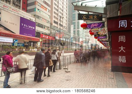 HONG KONG, CHINA - FEBRUARY 18: People waiting for the bus at the bus stop in Kowloon district on February 18, 2014 in Hong Kong, China.