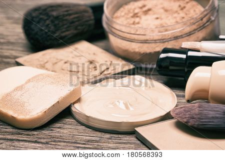 Make up products for flawless complexion: foundation, concealer, powder with cosmetic sponge and professional makeup brushes. Shallow depth of field, toned image