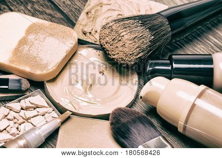 Make up products for flawless complexion: foundation, concealer, powder with cosmetic sponge and professional makeup brushes. Selective focus, toned image