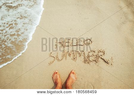 Leisure in summer - foot of man and Hello Summer text on sand at a tropical beach. Summer vacation concept. vintage color tone.