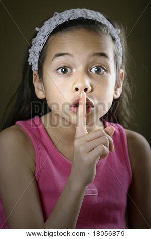 A girl placing her index finger on her lips in a request gesture for silence or secrecy.
