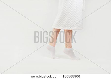 Slender beautiful female legs in socks walking on tiptoe, side view, isolated on white background