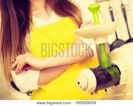 Woman In Kitchen With Juicer Machine
