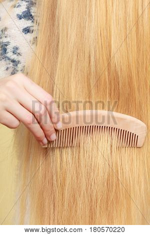 Haircare choosing best conditioner for tangled hairstyle concept. Blonde woman brushing her hair with comb