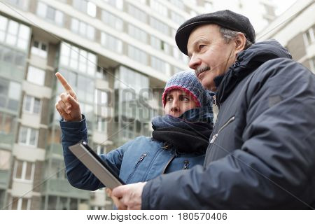 A Senior Man With A Tablet In His Hands Asks For Directions From A Stranger. Girl Shows Him With Fin