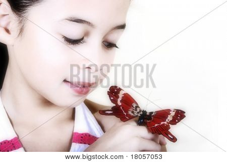 A young girl admiring a beautiful red butterfly.