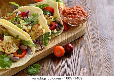 Tacos tortilla with roasted cauliflower beans vegetables and sauce, copy space