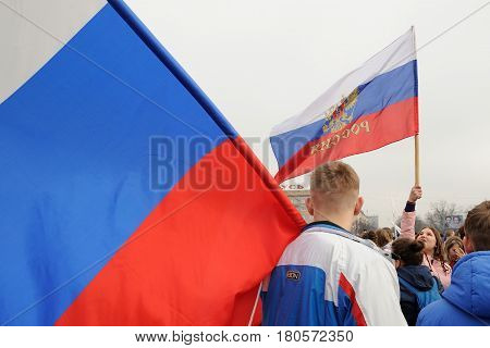 Orel Russia - April 08 2017: Meeting against terrorism. Young sportsman holding large Russian tricilor banner closeup