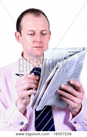 A businessman catching up on his newspapers, noting down the latest news, isolated against white.