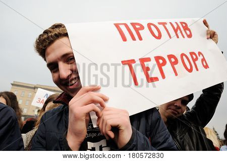 Orel Russia - April 08 2017: Meeting against terrorism. Young smiling men hiding behind anti-terrorism banner closeup