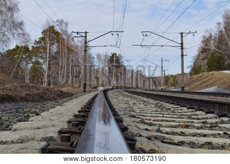 Rail closeup. Trans-siberian railway in Siberian taiga forest in spring. Novosibirsk Siberia Russia.