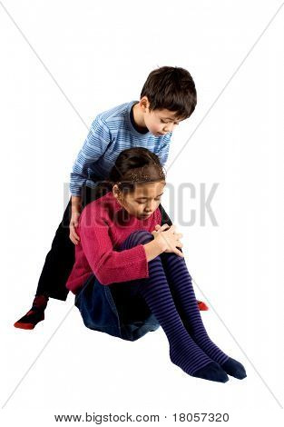 A young boy helping his sister up after she fell over and hurt her knee.