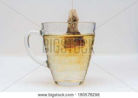 glass mug of tea with tea bag on white background