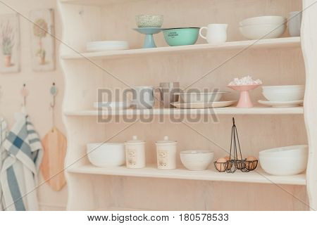 In the kitchen on the wall hangs a pink wooden shelf with utensils