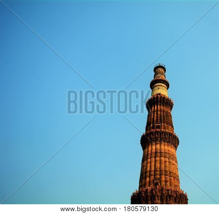 Looking up at the famous Qutub Minar, set against a clear open sky, and a deep blue atmosphere.