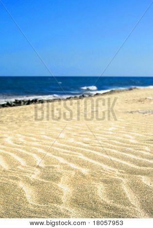 Rippled sand on a golden sandy beach with vast blue,cloudless sky.